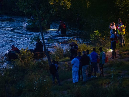 Search and rescue personnel stand along the bank of