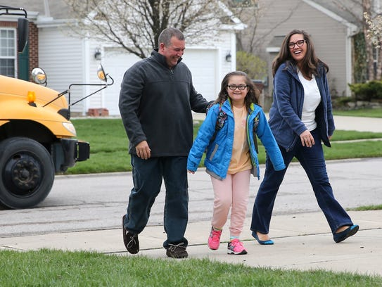 Madilyn Gers, center, walks up the driveway with her