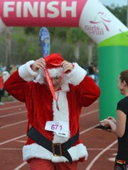 Christopher Shuchart dons a medal for completing the run. Hundreds of girls, plus reindeer, Santas, elves and a Grinch or two ran the 5K Reindeer Run Saturday morning at Community School of Naples, sponsored by Girls on the Run.