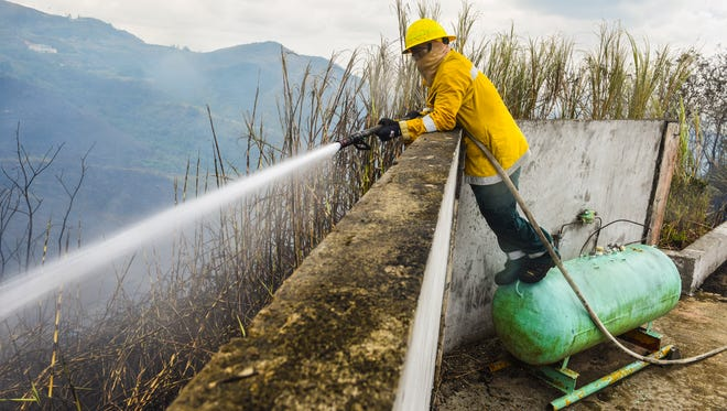 Guam Fire Department firefighter Frankie Baza stands on a liquid petroleum gas to gain a higher vantage point to extinguish a grass fire on the other side of a perimeter wall while battle the blaze that threatened residents along Turner Road on Nimitz Hill on Tuesday, March 27, 2018. Emergency personnel from the Guam Fire Department, Department of Agriculture's Division of Forestry and the Naval Base Guam Fire and Emergency Services, coordinate their efforts to snuff out the fire.