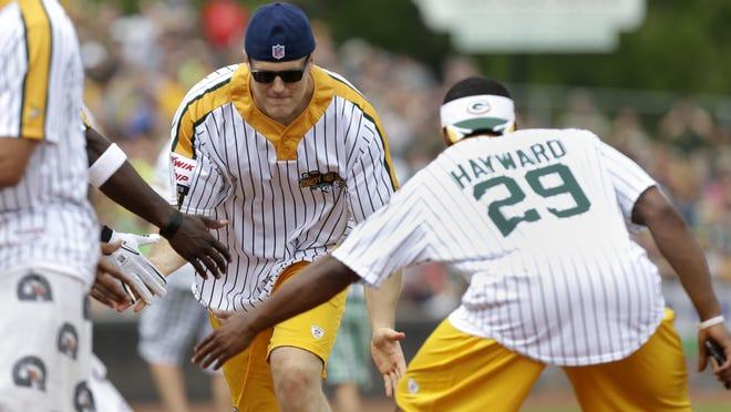 Clay Matthews is greeted by defensive teammates after he hit a home run at the Jordy Nelson Charity Softball Game Sunday at Neuroscience Group Field at Fox Cities Stadium in Grand Chute.