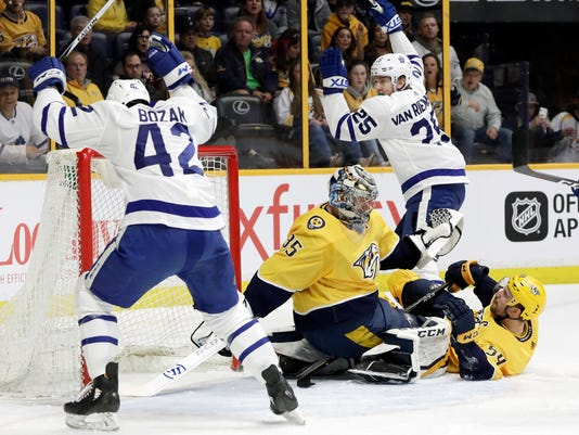 Toronto Maple Leafs left wing James van Riemsdyk (25) and Tyler Bozak (42) celebrate after van Riemsdyk scored a goal against Nashville Predators goalie Pekka Rinne (35), of Finland, in the first period of an NHL hockey game Thursday, March 22, 2018, in Nashville, Tenn. (AP Photo/Mark Humphrey)