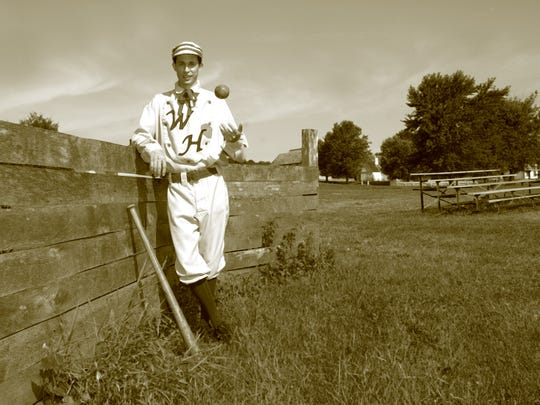 Aaron Haywood, 30, shows off a 1870's style baseball uniform from the Walnut Hill Blue Stockings baseball team at Living History Farms in Urbandale in 2011.