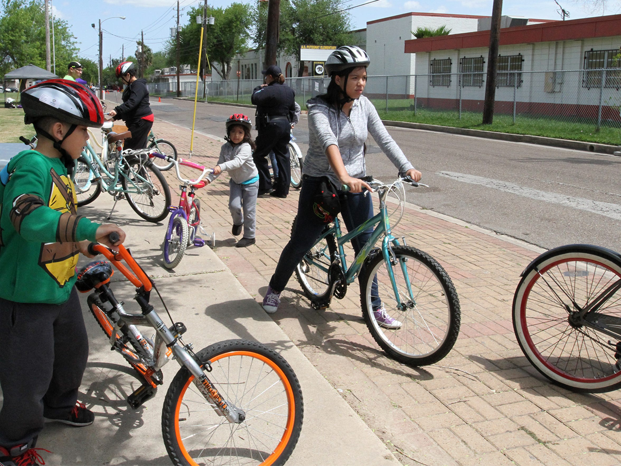 Parents and children start out on a bike ride along closed streets during a CycloBia Sunday, March 20 in Brownsville, TX.