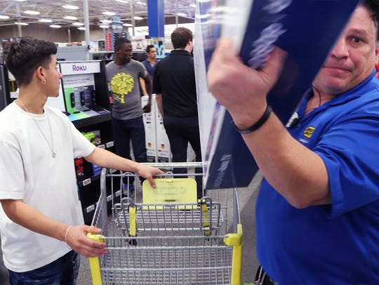 Best Buy sales consultant Scott Jordan (right) moves