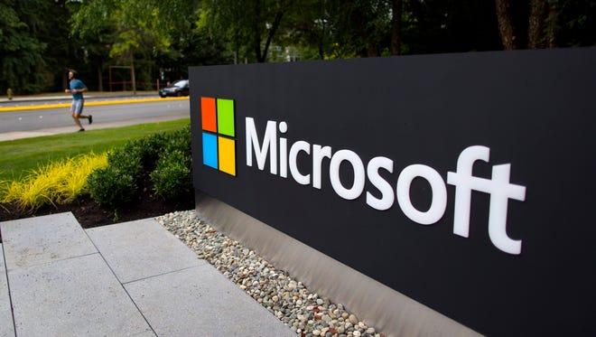 A jogger runs past signage displayed at the Microsoft Corp. campus in Redmond, Washington, U.S., on Wednesday, Sept. 4, 2013.