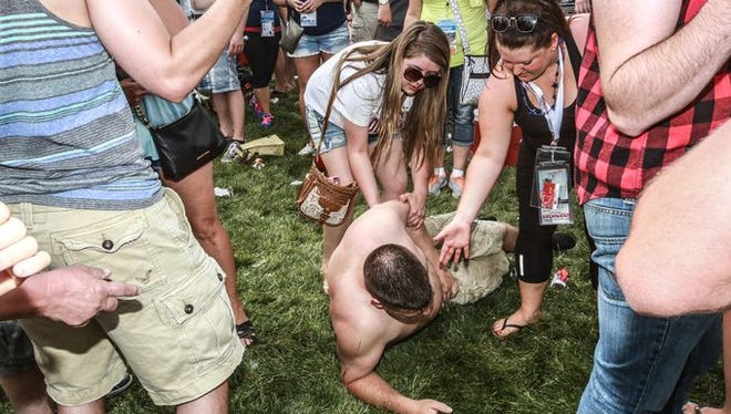 A intoxicated unidentified man is assisted by unidentified women at the Indianapolis 500 Coors Light Carb Day.
