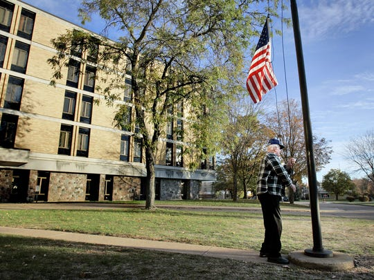 A World War II veteran raises the flag at the Wisconsin