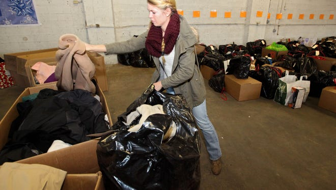 Volunteer, Kelsey Coulter of Bridgewater helps separate donated coats. The United Way of Northern Jersey held its annual gift giving event at their warehouse off Chimney Rock Road in Bound Brook. Coats and other holiday gifts were distributed to families. The event was held Saturday, December 19, 2015. Mary Iuvone/For The Courier News