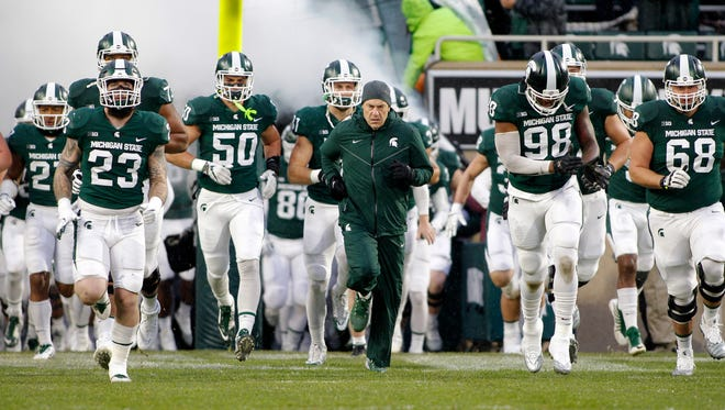 Michigan State players and coach Mark Dantonio, center, run onto the field before the game against Maryland on Saturday, Nov. 18, 2017, at Spartan Stadium.