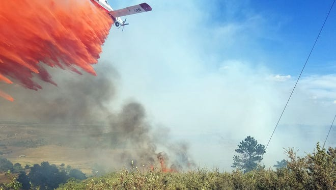 A Single Engine Air Tanker drops a load of fire retardant on the Hertha Ridge Fire Wednesday, Aug. 17, 2016, near Carter Lake.