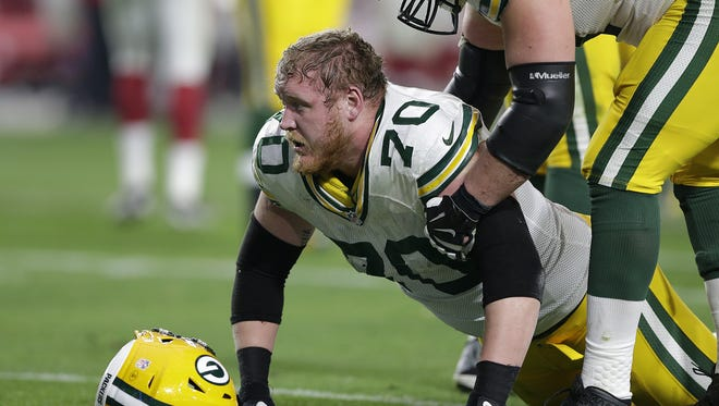 Green Bay Packers guard T.J. Lang (70) slowly gets up after getting hit against the Arizona Cardinals at University of Phoenix Stadium.