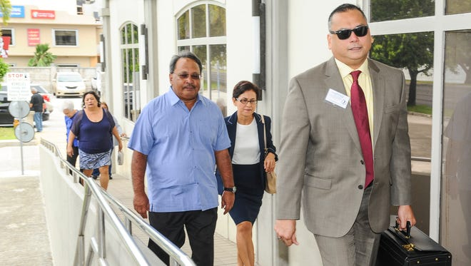 Airport consultant Francisco Roberto Santos, in blue shirt, prepares to enter the District Court of Guam with his attorney, Jay Arriola, right, on Thursday, Oct. 15.