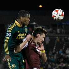 Sep 13, 2014; Commerce City, CO, USA; Portland Timbers defender Alvas Powell (2) heads the ball against Colorado Rapids defender Shane O'Neill (27) during the second half at Dicks Sporting Goods Park. The game ended in a tie 2-2. Mandatory Credit: Troy Babbitt-USA TODAY Sports