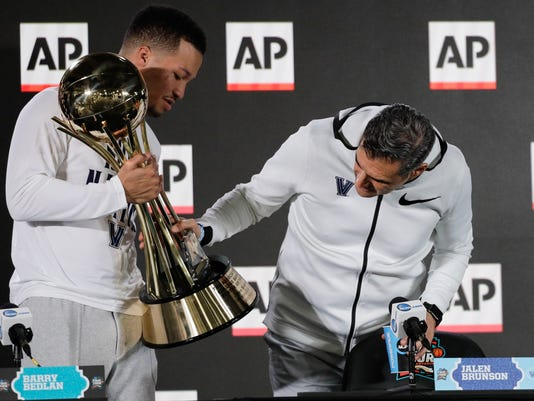 Villanova head coach Jay Wrightlooks at Jalen Brunson's AP Player of the Year trophy at a news conference at the Final Four NCAA college basketball tournament, Thursday, March 29, 2018, in San Antonio. (AP Photo/David J. Phillip)