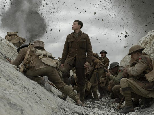 """This image released by Universal Pictures shows George MacKay, center, in a scene from """"1917,"""" directed by Sam Mendes. On Monday, Jan. 13, the film was nominated for an Oscar for best picture. (François Duhamel/Universal Pictures via AP)"""
