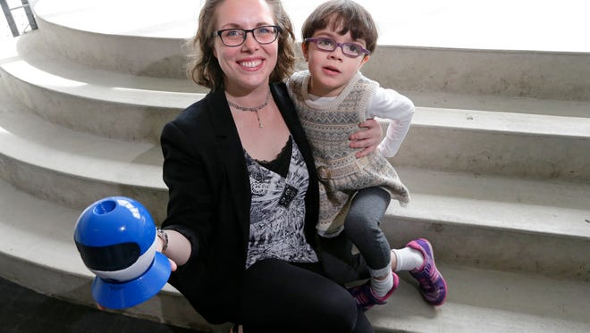 Christine Carr, who is graduating from Milwaukee Institute of Art & Design, holds a drone prototype she created to help parents keep track of autistic children. She's pictured with her 6-year-old daughter, Lillian, who has autism.