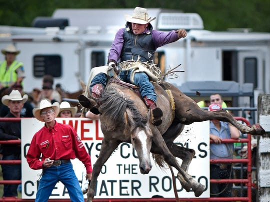 Wyatt Christensen hangs on during bareback competition during the Clearwater Rodeo presented by the Silver Bullet Saddle Club Friday, Aug. 19, 2016