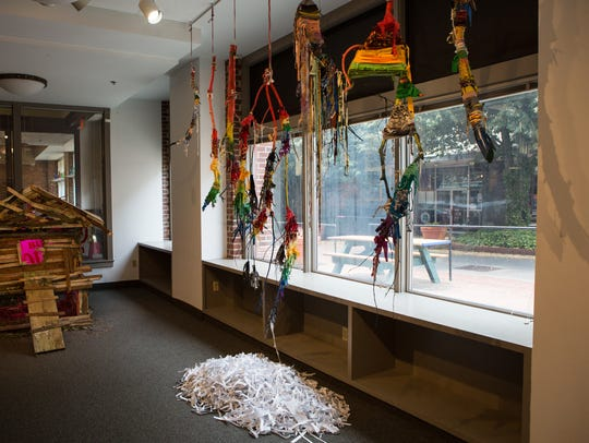 A view of the interior of SU Art Galleries Downtown Campus. The work displayed in the background is by Amber Robles-Gordon.