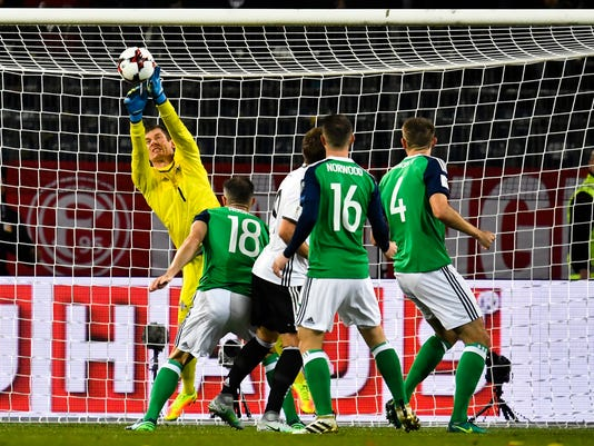 FILE - In this Tuesday, Oct. 11, 2016 file photo, Northern Ireland's goalkeeper Michael McGovern, right, saves the ball during their World Cup Group C qualifying soccer match against Germany in Hannover, Germany. Goalkeeper Michael McGovern will represent Northern Ireland on Thursday, Nov. 9, 2017 in a playoff round first-leg game against Switzerland in Belfast, for his fifth World Cup qualifying game this season. Yet in the same period he has not played a single game in England's second division for his club Norwich.(AP Photo/Martin Meissner, file)