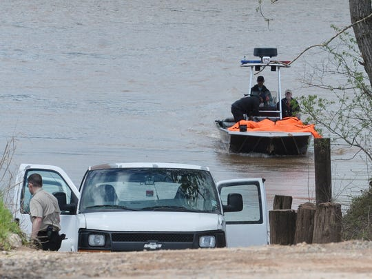The coroner's van waits at the bank of the Red River