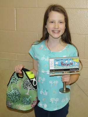 Elise Miller of Green Springs Elementary holds her winning Earth Day billboard design.