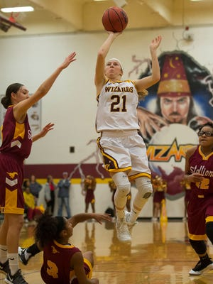 Windsor High School senior Michaela Moran (21) gets past Sierra defenders for a shot on Tuesday, Feb. 27, 2018, at Windsor High School, in Windsor, Colo.