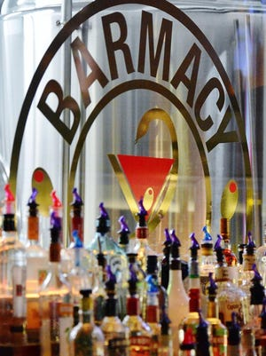 A club logo is displayed on the window behind bottles of liquor at Barmacy on West Market Street in Akron where the Ran Barnaclo Cosa Nostra Comedy Show will be featured 8-9:30 p.m. Saturday.