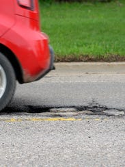 A car drives over an Aurelius Road pothole on Tuesday, April 26, 2016, in Lansing.