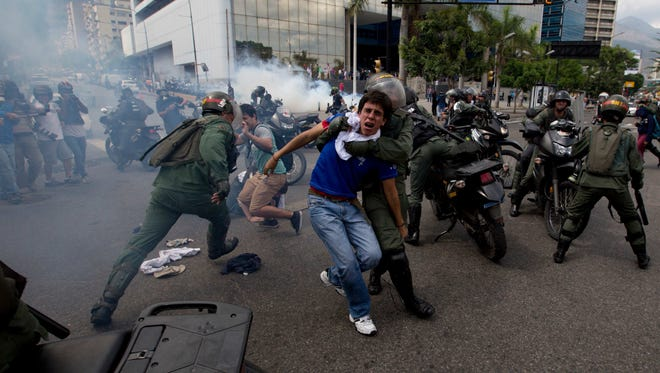 Bolivarian National Guardsmen detain anti-government demonstrators during clashes at a protest in Caracas, Venezuela, on May 14, 2014.