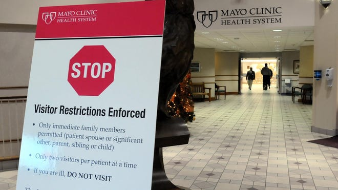 A sign in the entry of the Mayo Clinic Health System hospital in Mankato, Minn., spells out visitor restrictions implemented to curb the spread of influenza. The Mayo Health System recently put the restrictive policy in place in 15 hospitals in southern Minnesota and South Dakota because of the flu outbreak.