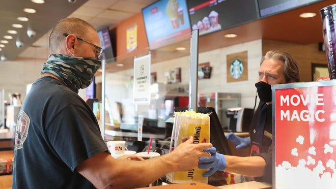 Rick Zuponcic of Mantua buys a bag of popcorn before watching a movie at Cinemark on Friday, Aug. 21, 2020 in Cuyahoga Falls, Ohio.