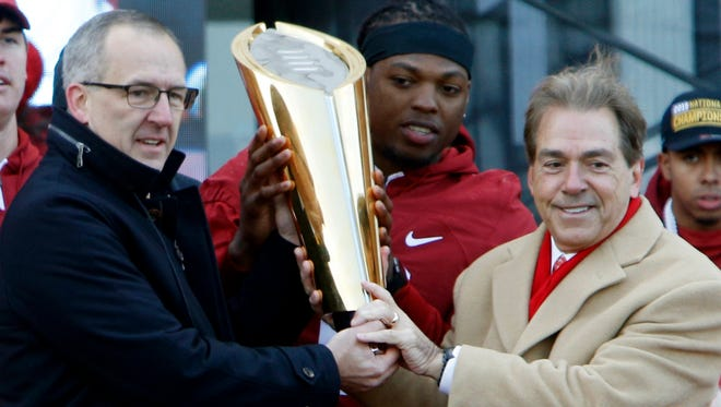Southeaster Conference commissioner Greg Sankey presents the national championship trophy to Heisman trophy winner Derrick Henry and Crimson Tide coach Nick Saban, Saturday, Jan. 23, 2016, in Tuscaloosa, Ala. Alabama football fans turned out by the thousands to celebrate the Crimson Tide's fourth national championship in seven years. (AP Photo/Hal Yeager)