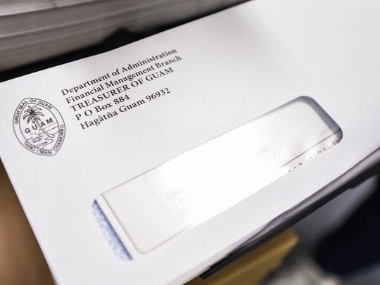 In this Sept. 15, 2017, file photo, an envelope containing a tax refund check drops into a bin with other envelopes at the Department of Administration treasurer's window.