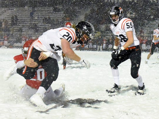 St. Cloud Tech's running back Scott Kippley is brought down by Elk River's  tight end Rey Roske during the first half of the Section 6-5A championship game Friday, Nov. 3, in Buffalo.