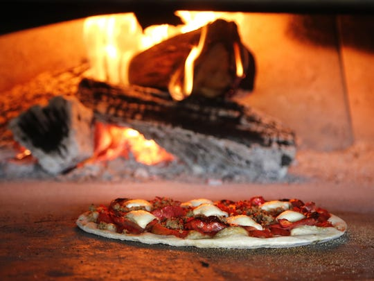 A Carni pizza cooks in the wood-fired brick oven Tuesday, June 30, 2015, at Sylvia's Brick Oven, 625 Columbia Street in Lafayette. The Carni features house made Italian sausage, spicy capicola, genoa salami, peppadew peppers and basil.