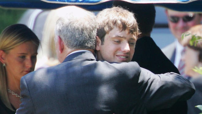John Ramsey hugs his son, Burke, facing camera, at the graves of his wife, Patsy, and daughter JonBenet, during services for his wife at the St. James Episcopal Cemetery in Marietta, Ga. A judge has declined to dismiss a $750 million defamation lawsuit filed against CBS by Burke Ramsey. The Boulder Daily Camera reports a circuit court judge in Michigan on Friday, Jan. 5, 2018, denied a motion by CBS and other defendants who asked that he toss the case.