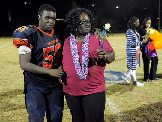 Malik Johnson hug his mom, Marinda Johnson, after being presented during senior night Friday, Oct. 23, 2015, at Lighthouse Christian School.