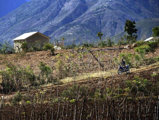 A local cyclist traverses a dirt road down a hillside