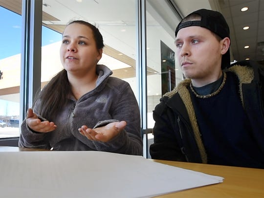 Lindsy Shuff, left, and her fiancé, Cody Spangler, read and talk about court documents relating to the car that she bought at the York County Drug Task Force Auction.