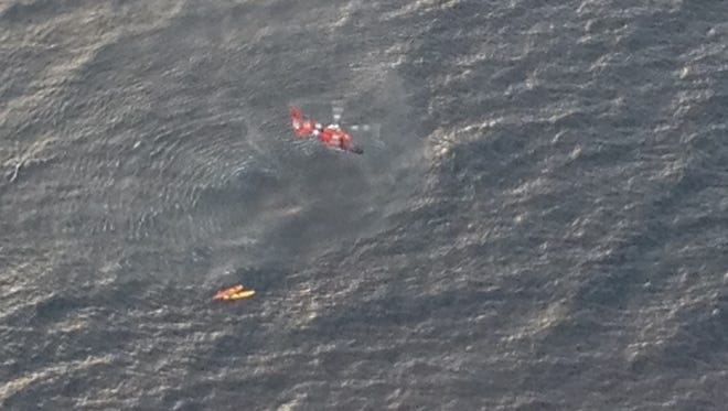 A Coast Guard Dolphin helicopter from Air Station Traverse City, Mich., prepares to rescue three kayakers from Whaleback Shoal in Green Bay on Friday morning. The U.S. Coast Guard, along with the Royal Canadian Air Force and several local agencies assisted in the search and rescue of three kayakers reported missing Thursday evening.
