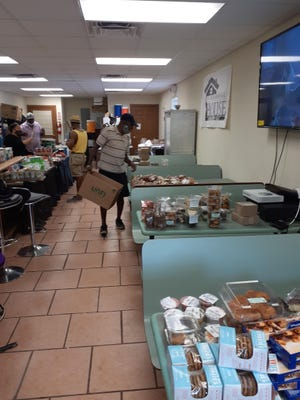 Coswell Depeiza arranges food on a table for members of the community to collect at the Neighborhood House food distribution site at 739 NW Fifth Ave. operated by members of the Beta Pi chapter of Omega Psi Phi Fraternity Inc.