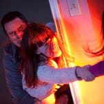 "This photo provided by Twentieth Century Fox shows, Sam Rockwell, left, as Eric Bowen and Rosemarie DeWitt, center, as wife Amy, desperately trying to hold on to Kennedi Clements, right, their youngest daughter Madison, who's been targeted by terrifying apparitions in the film, ""Poltergeist."""