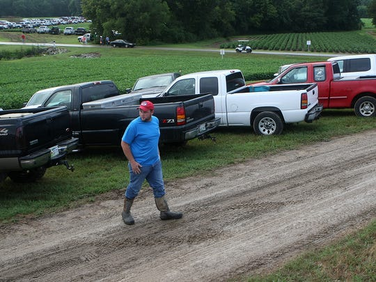 Ty Wilson looks to cross a muddy road during the 29th Milan No-Till Crop Production Field Day in Milan, Tenn., on Thursday, July 28, 2016.