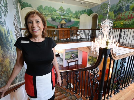 Mary Ann Fisher, the director of wedding and special events since 2010, stands on the second floor landing of the grand staircase. The mural wrapped along the walls of two floors, painted in 1999 by a local Italian artist, has 7 hidden frogs in the painting.