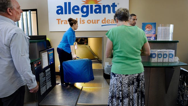 Allegiant Air workers take baggage from passengers for a flight out of Provo, Utah, Wednesday afternoon, Aug. 31, 2016. People are increasingly flying out of small airports in Provo and Ogden to take advantage of less expensive tickets and fewer crowds.