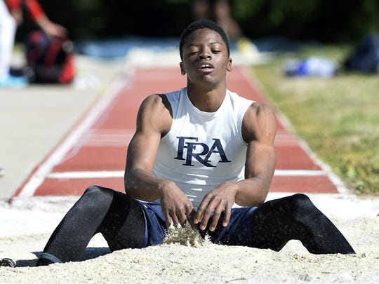 Eric Stoxstill-Diggs of Franklin Road Academy sits in the sand pit after his final jump in the boys long jump event during the Highland Games Track and Field Relays at Franklin Road Academy on Saturday, March 28, 2015, in Nashville.