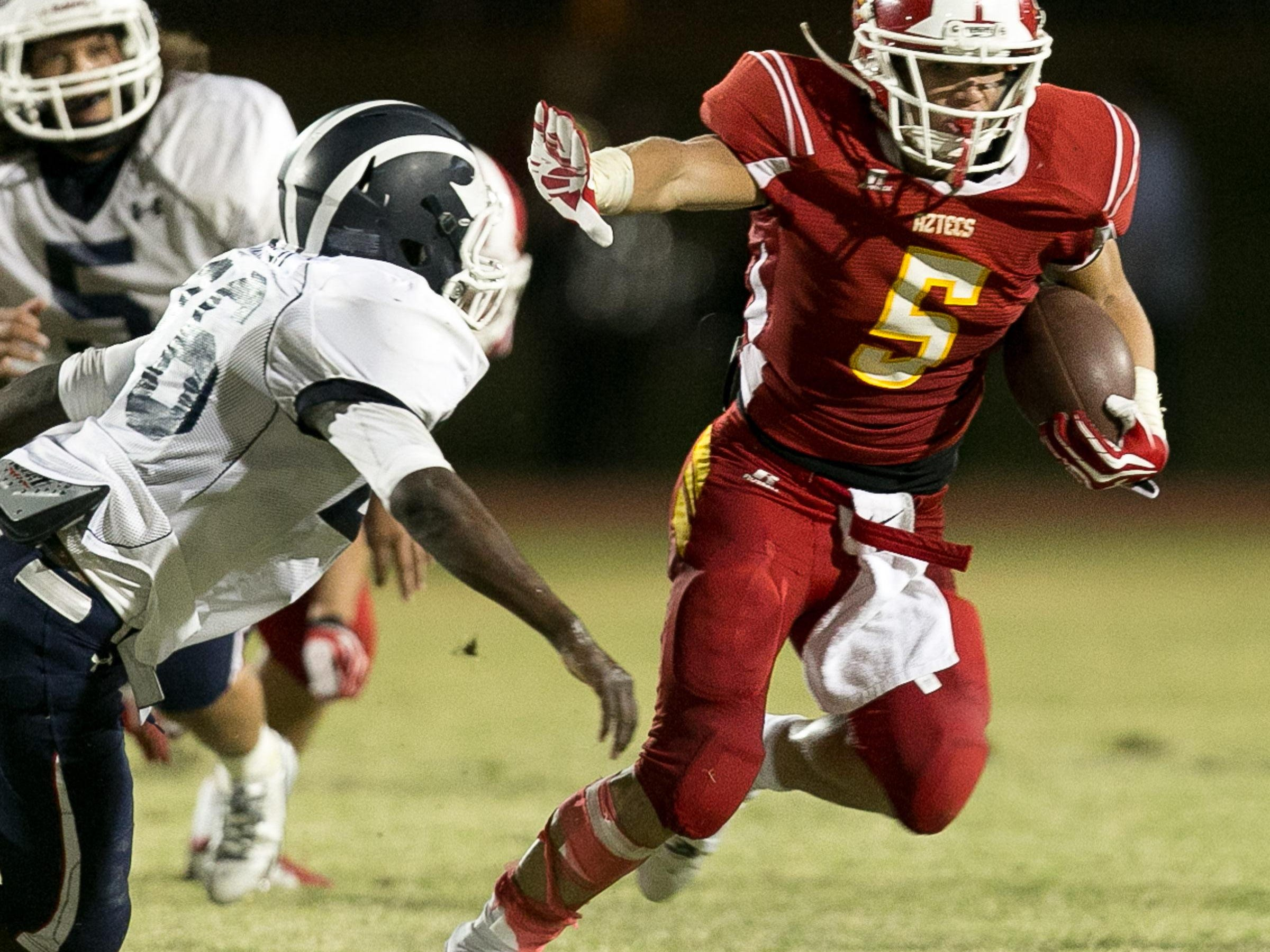 Palm Desert's Trae Riek (right) stiff-arms a Redlands defender back in 2013 when the Terriers defeated the Aztecs 35-29. Friday, Redlands returns to Palm Desert High School as the Aztecs try to fend off another loss to the Terriers.