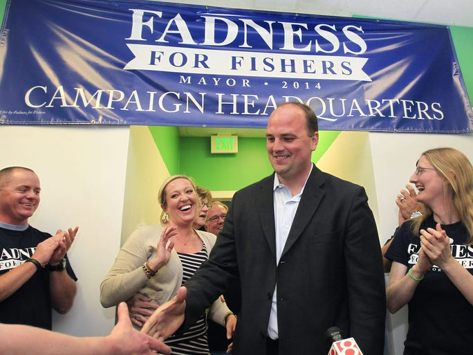 Victorious Fishers Town Manager Scott Fadness walks into his campaign headquarters to the accolades of supporters about 9:45 shortly after he was declared the winner of the race to become Fishers mayor on Tuesday, May 6, 2014. At left is his wife Aunna, who is reacting to his announcement that they are expecting their first child. An all-GOP field of 6 candidates were seeking to become the first mayor of Fishers. Former Town Council member and president Walt Kelly, came in second.