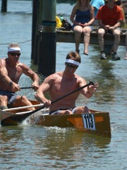 "Second place (adjusted) pro winners Pete Jenks, left, and Casey Jenks crank it to the finish line. The 39th Annual Great Dock Canoe Race, with a ""Hunger Games"" theme, filled the bay with canoes and the dock with spectators at Crayton Cove on Saturday, May 9, 2015."